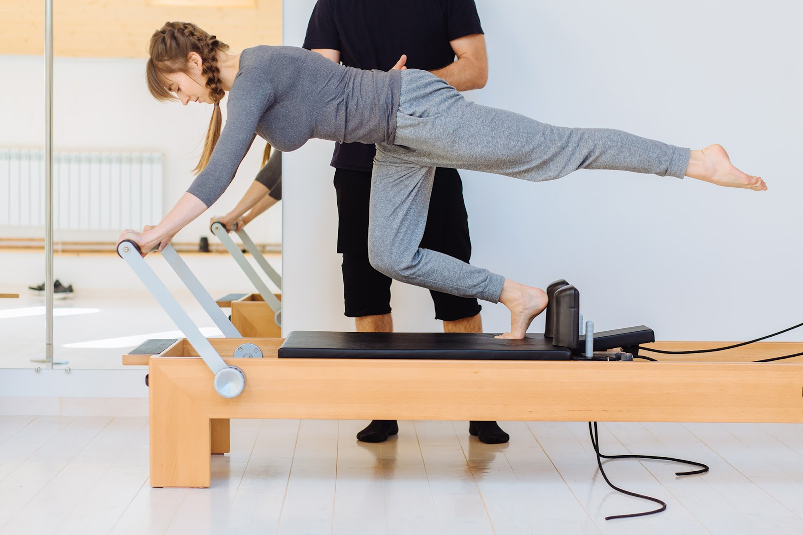 Male Pilates instructor teaches female student challenging exercise on pilates reformer.