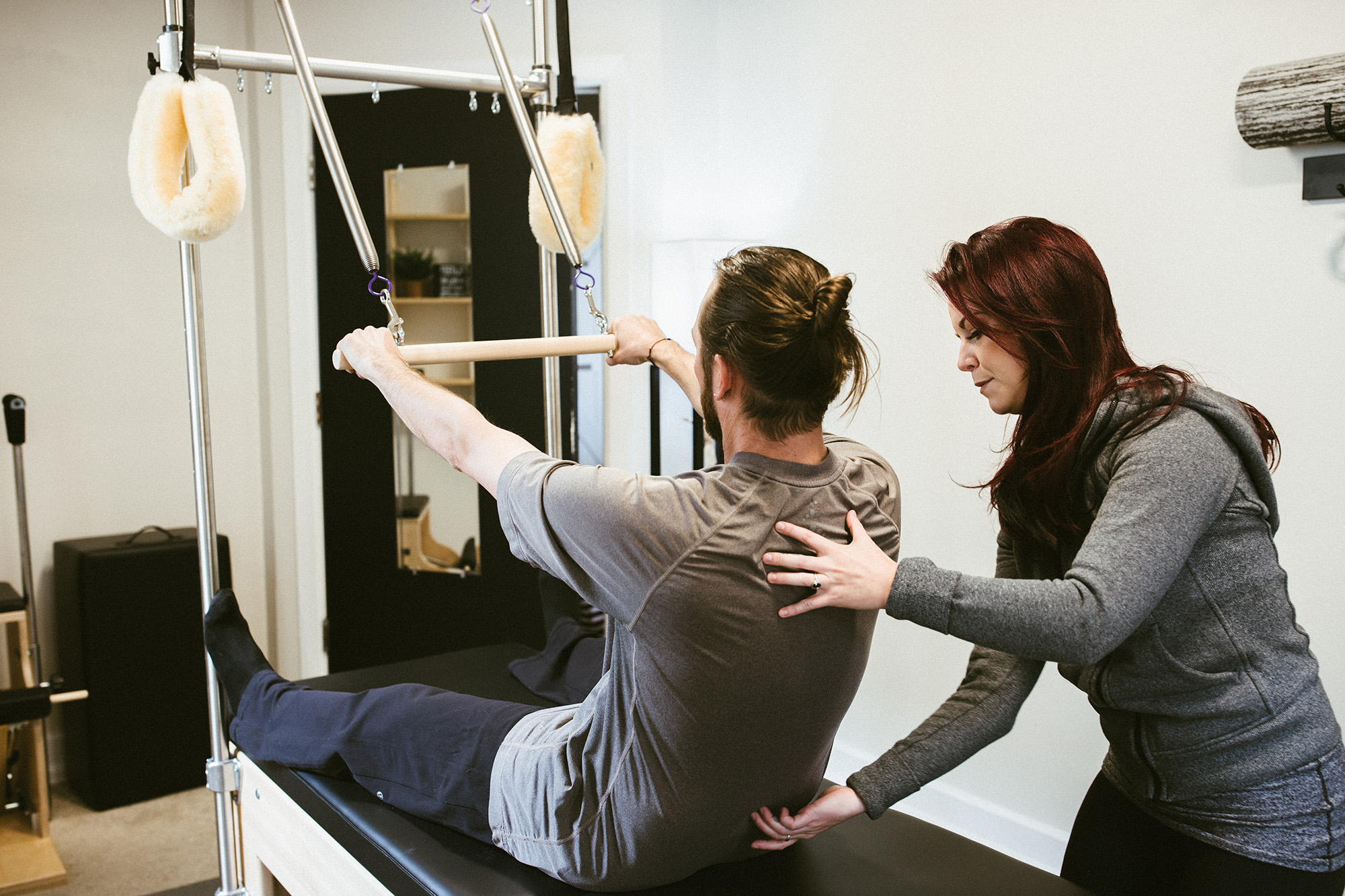 A red headed pilates instructor teaches attractive male student rolldowns on the pilates cadillac.