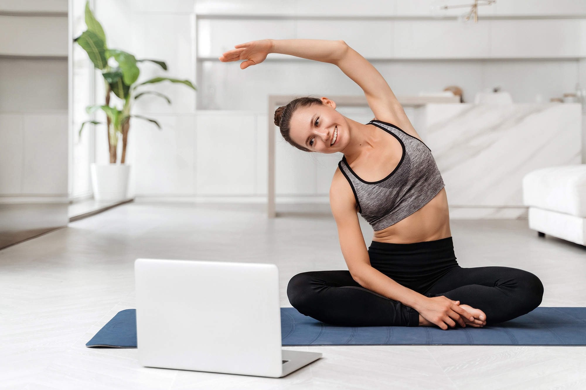 A pretty young woman in a gray sports bra and black leggings sits cross legged on a mat in front of a laptop practicing a virtual pilates class.