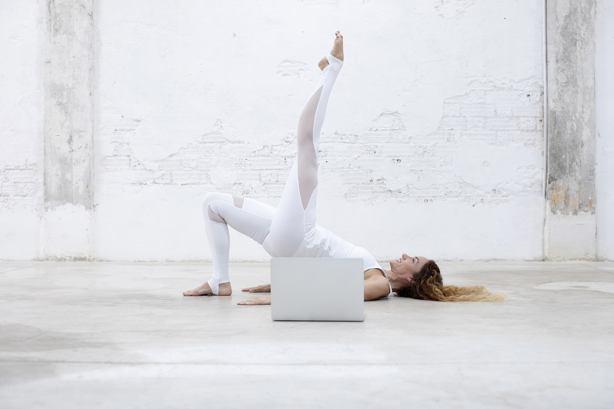 An attractive woman practicing pilates bridge exercise at home from a virtual session.