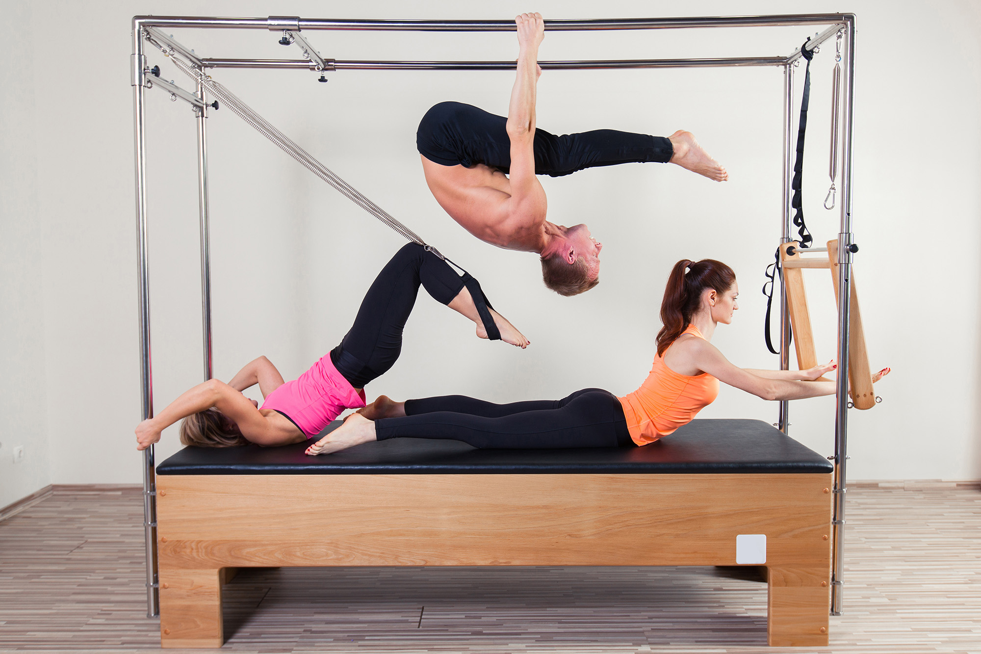 Two young, athletic women and one man all performing acrobatic pilates exercises on the same trapeze table.