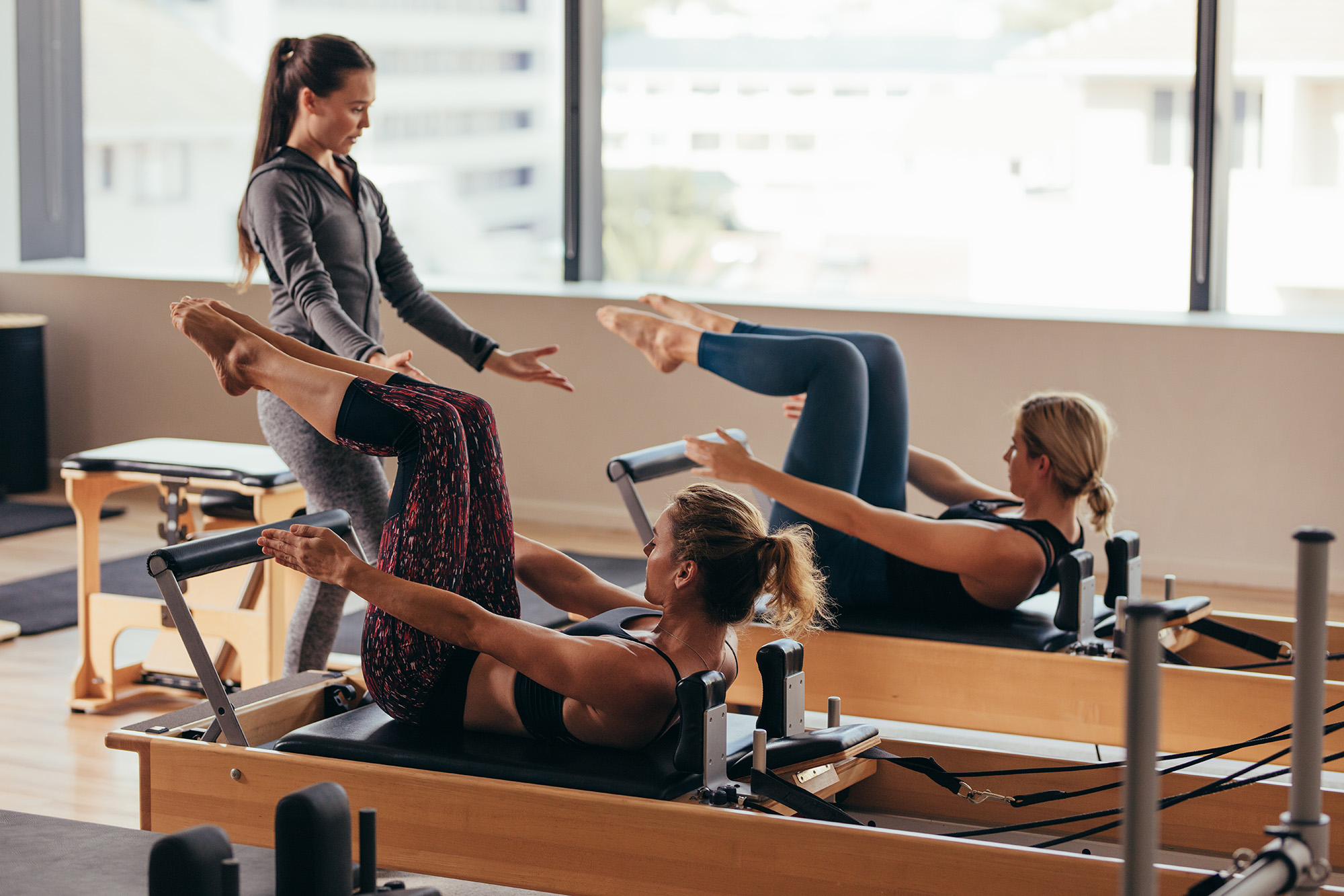 An attractive pilates instructor teaches two fit women a semi-private pilates session.