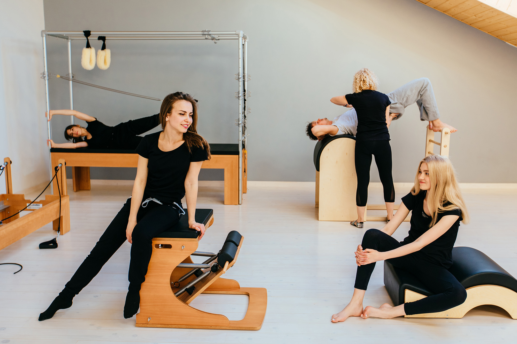 four people wearing all black practicing pilates equipment. The trapeze table, pilates chair, spine corrector and ladder barrel