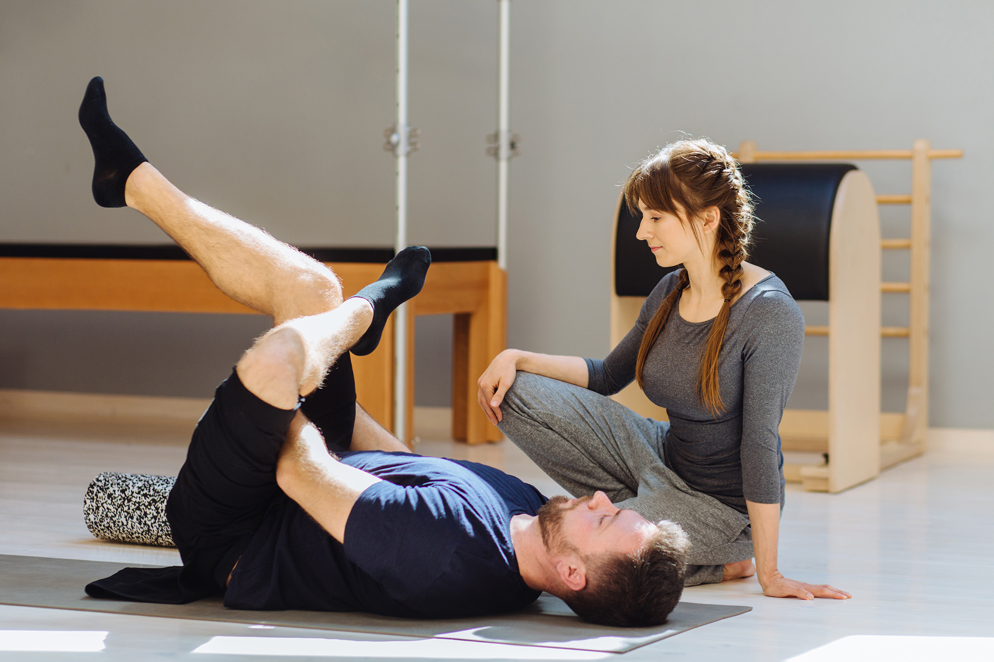 A young woman pilates instructor teaching the rehabilitation pilates method to a man lying on a mat in a pilates studio