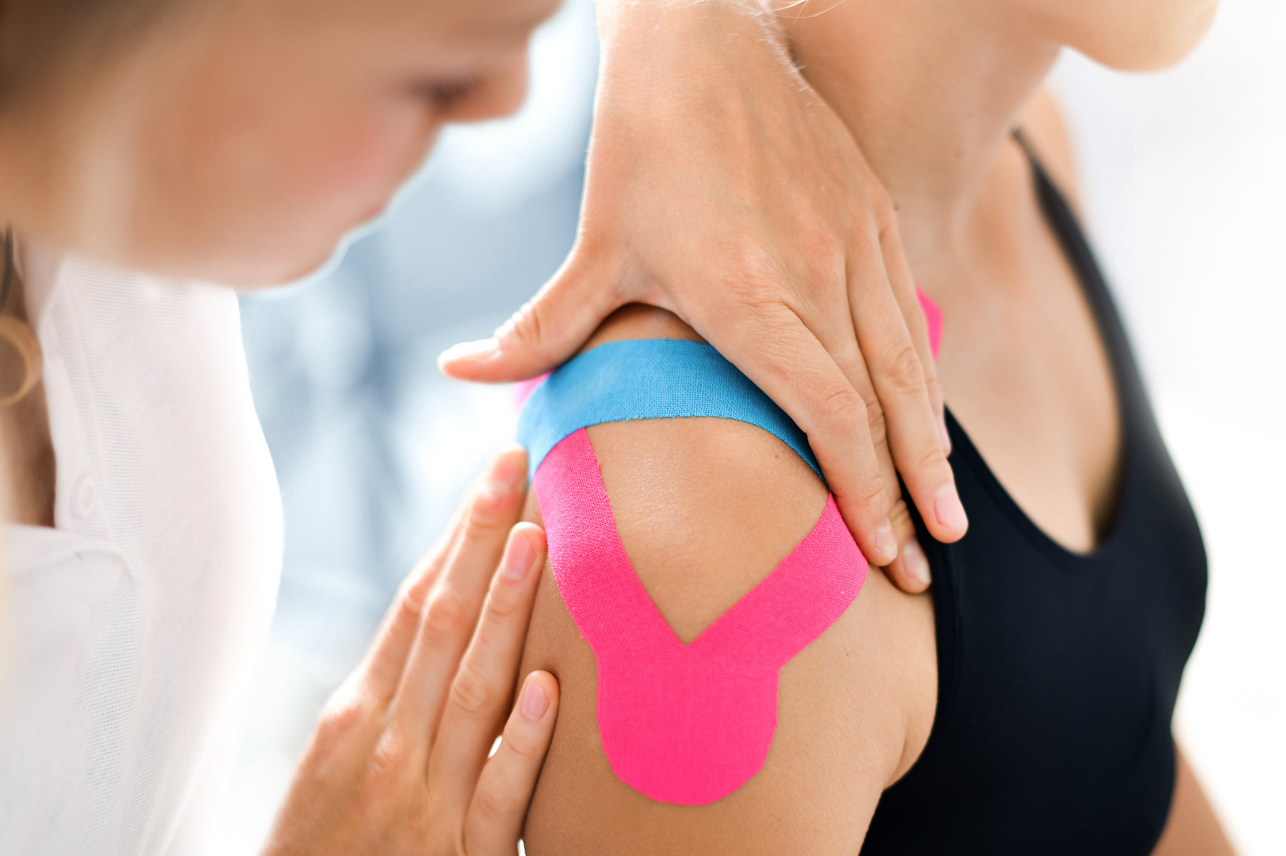 pilates instructor applying pink and blue kinesiology tape to a shoulder of a woman in a black sports bra