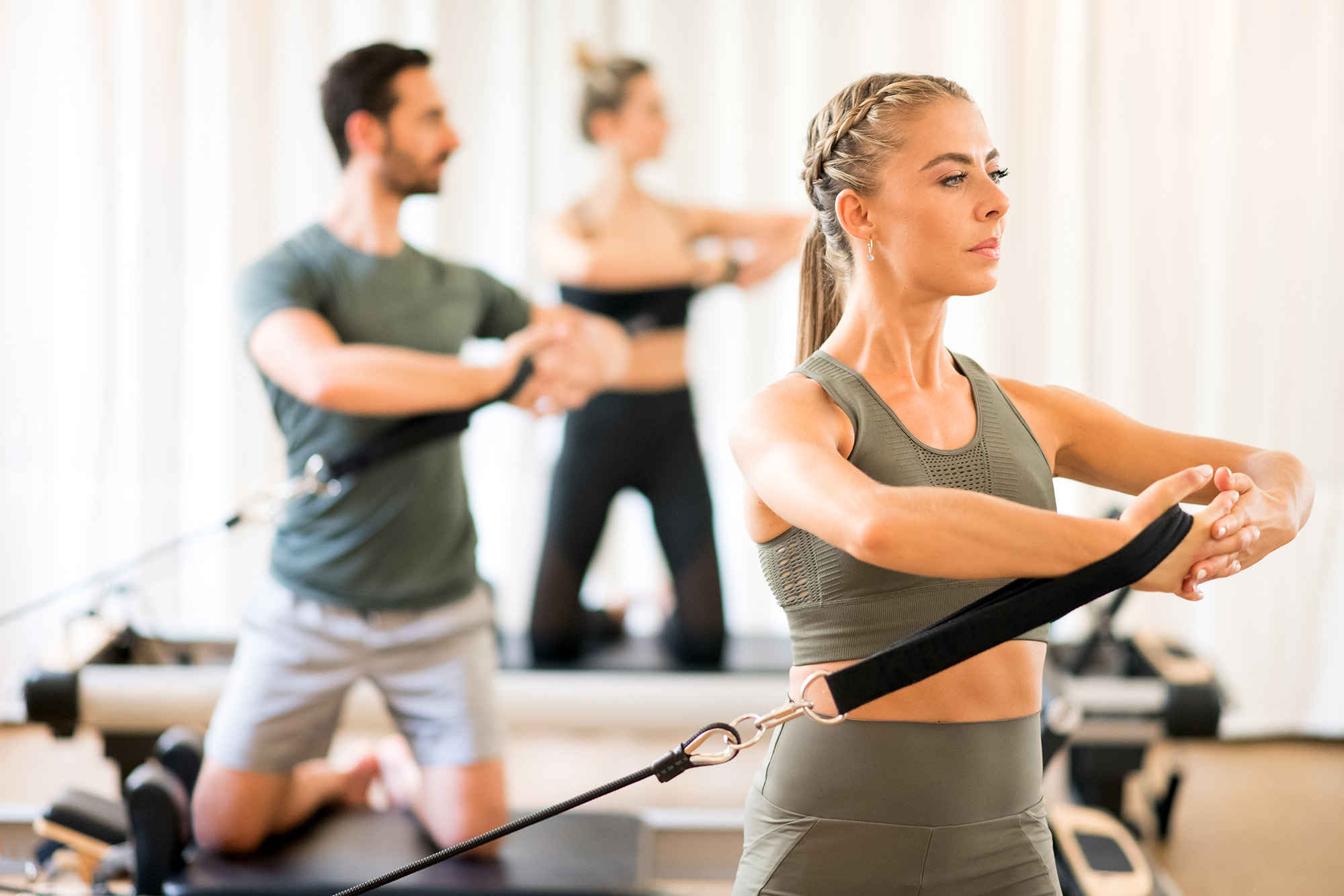 two young pretty blonde women and one brown haired man practicing reformer pilates classes in spine rotation