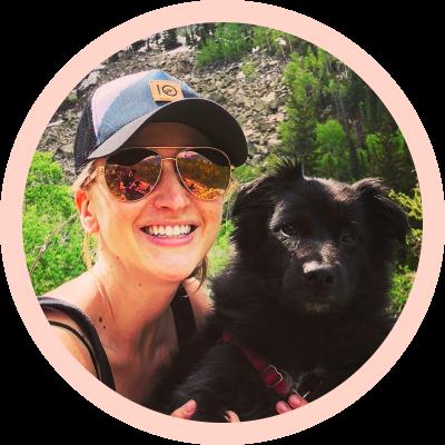 a pretty white blonde female in a baseball hat and sunglasses with a cute black dog