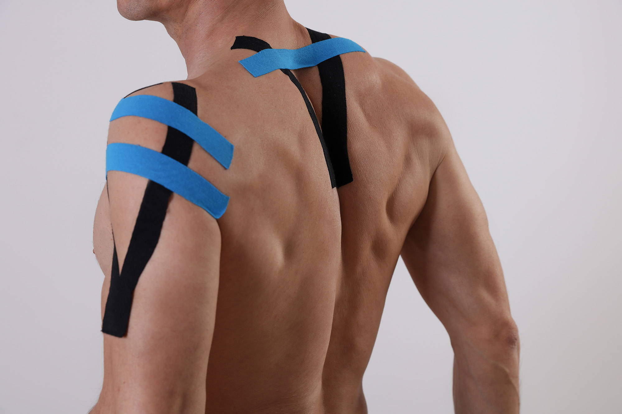 The back of a shirtless muscular man with kinesiology tape on his shoulder and back.
