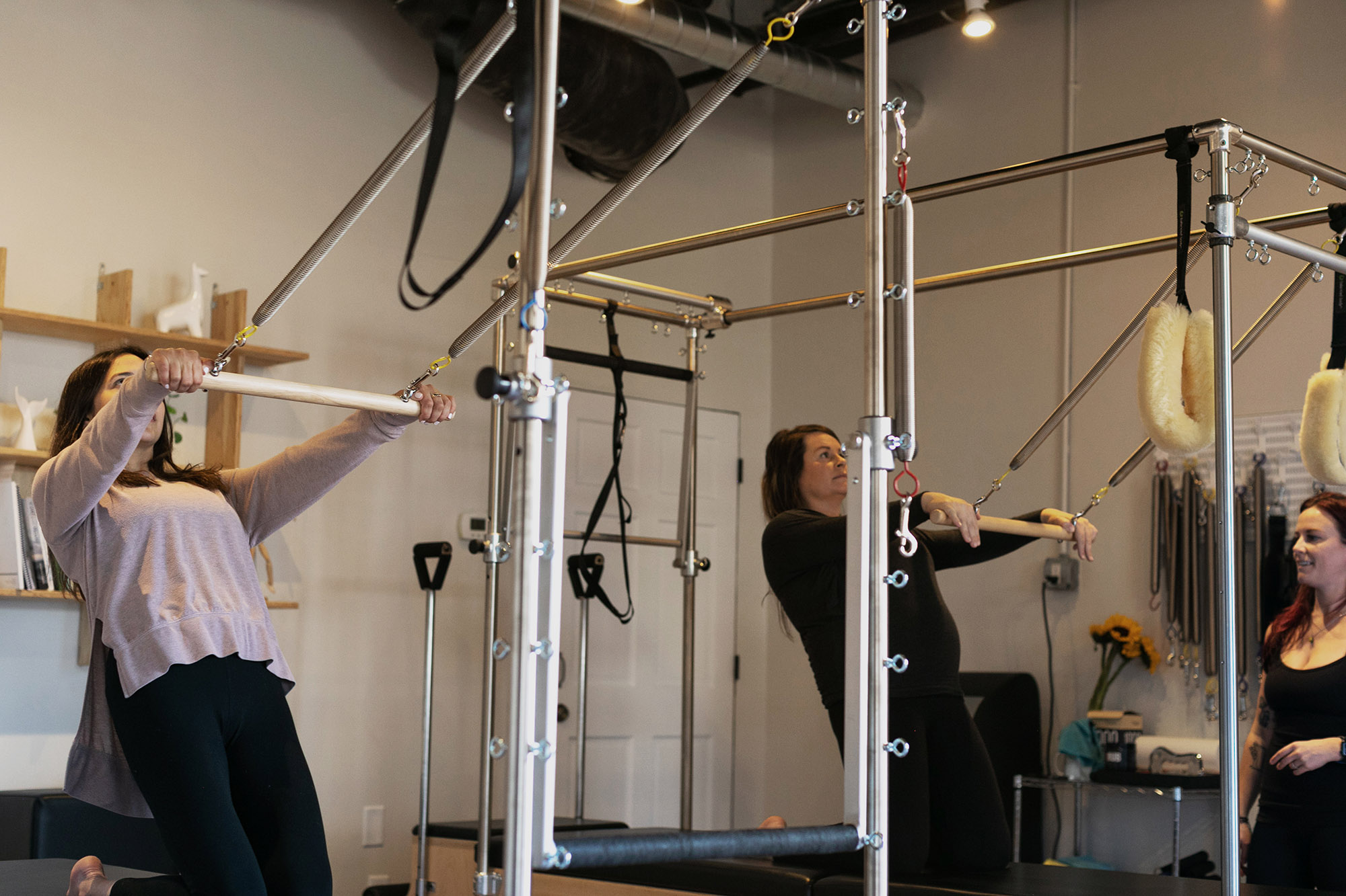 two female students practice thigh stretch on the pilates cadillac in a semi private class