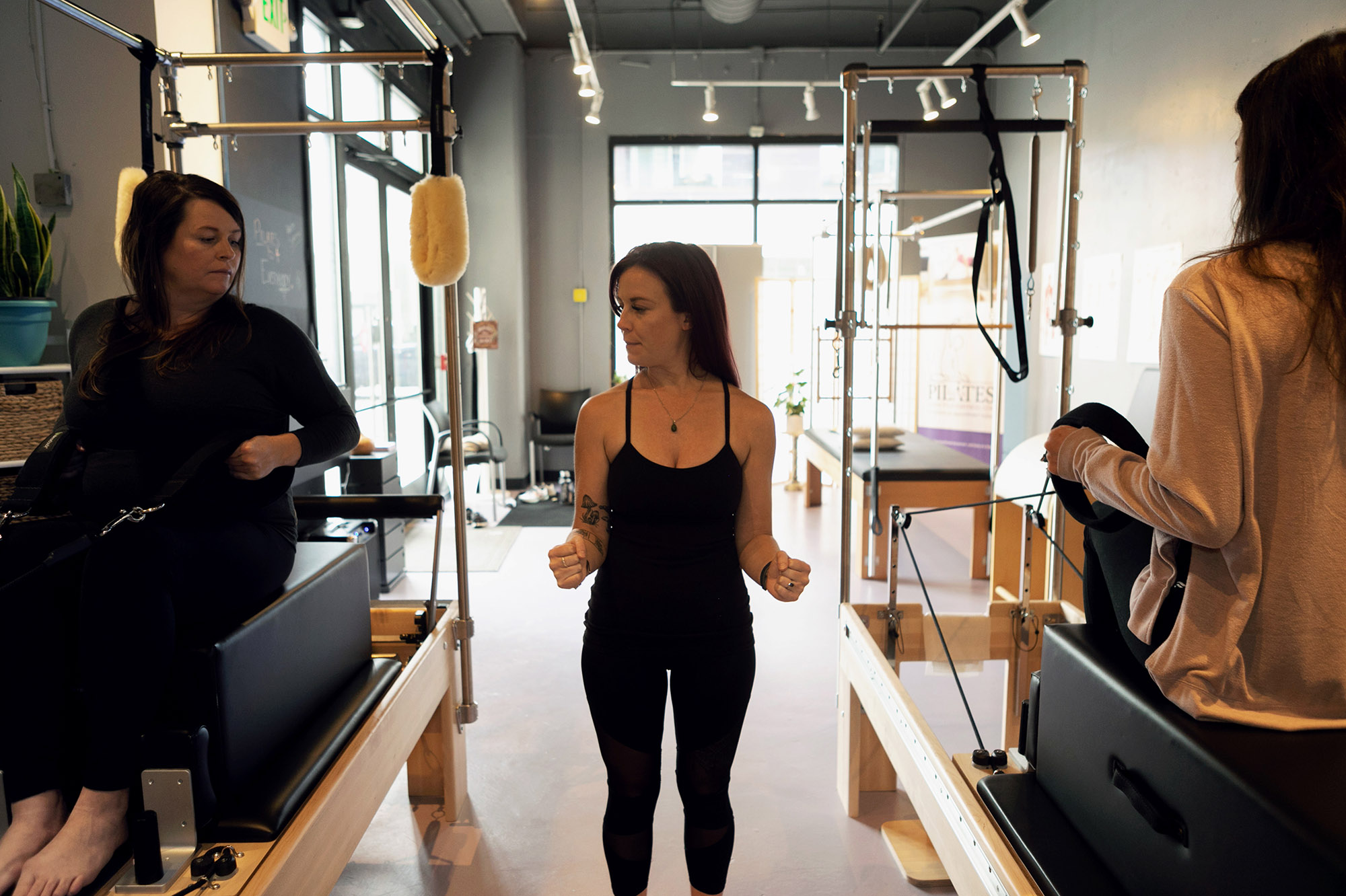 Two students practicing pilates in a semi-private while pilates instructor cues movements