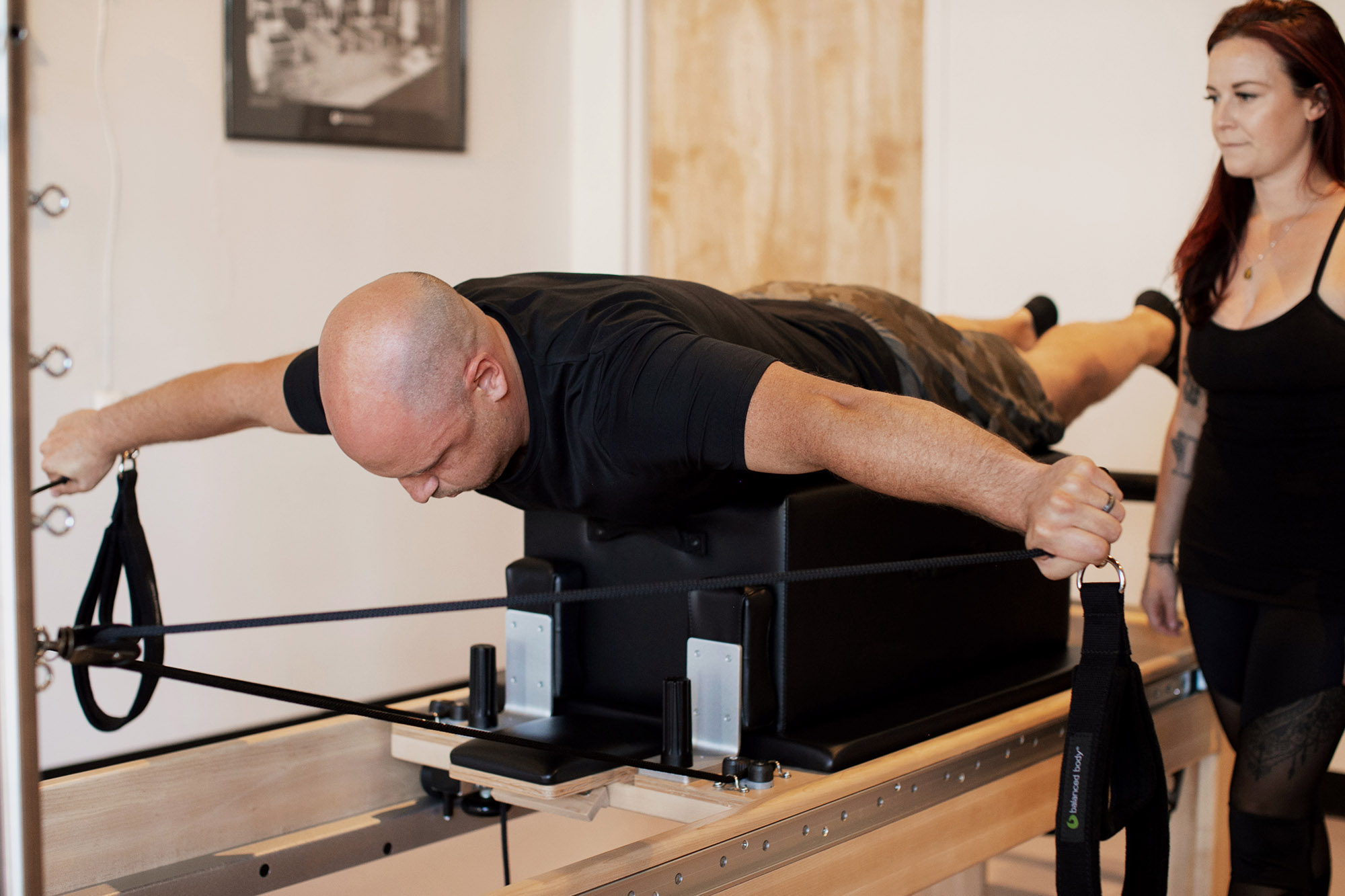 Male pilates student performs pulling straps on pilates reformer while female instructor teaches him.