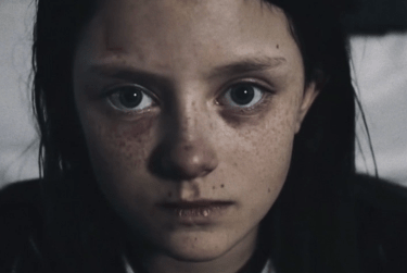 Shot from the a video of a girl with dark hair and freckles staring straight at the camera.