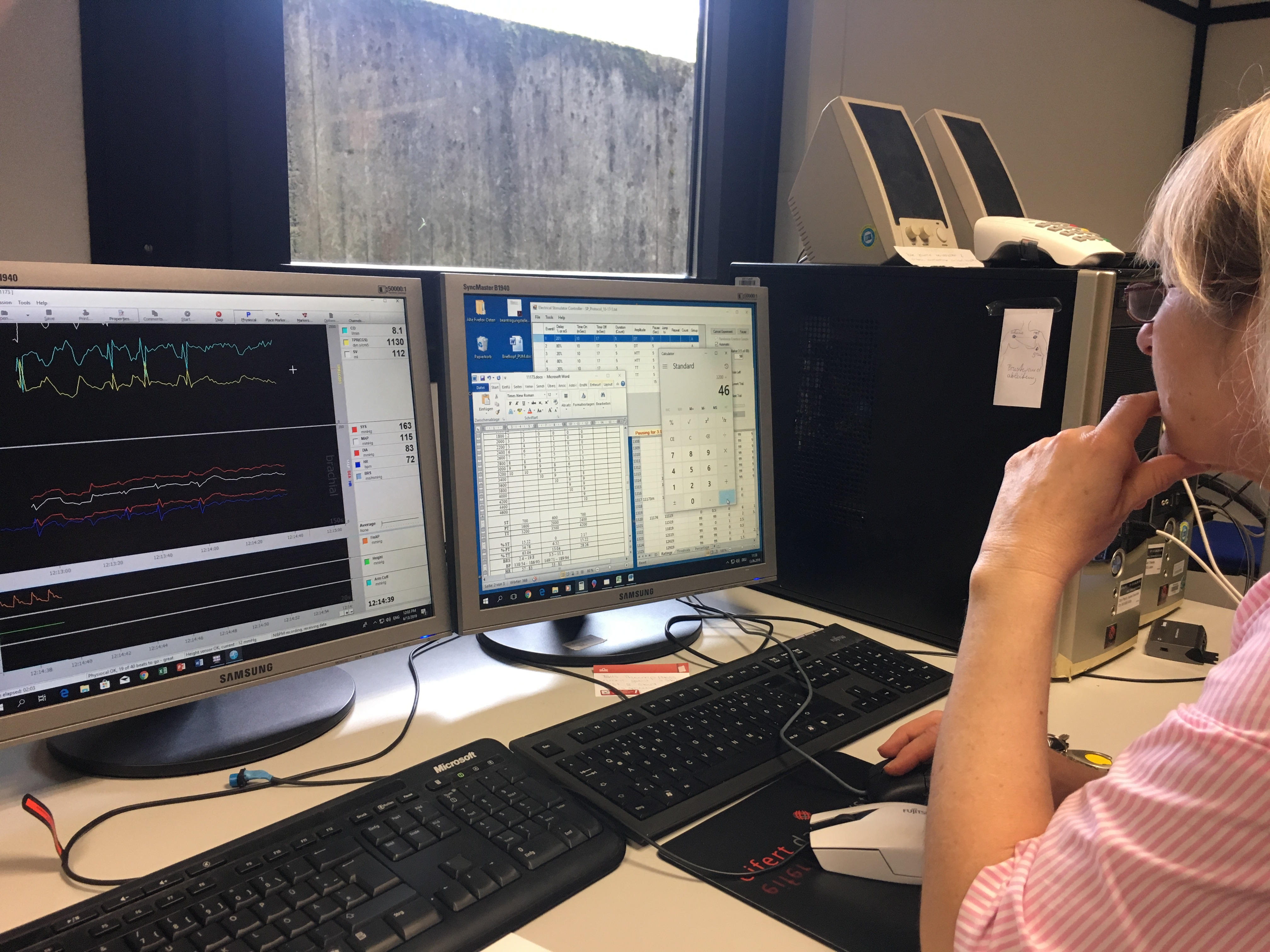 researcher looking at two screens