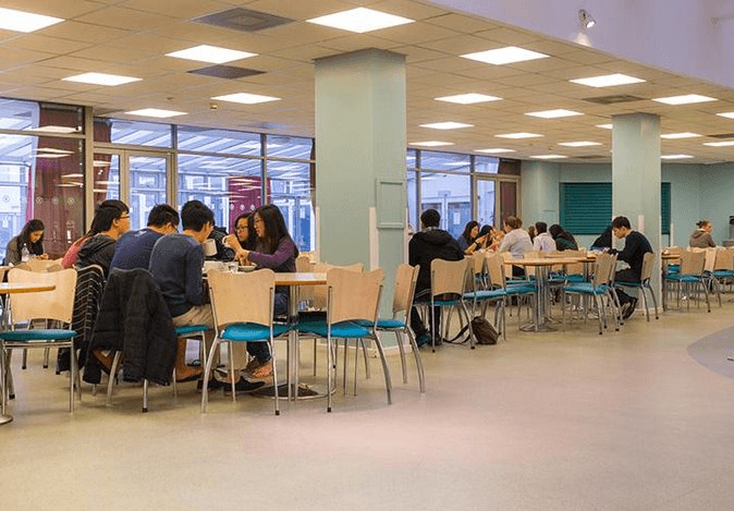 students sitting around tables in a cafeteria
