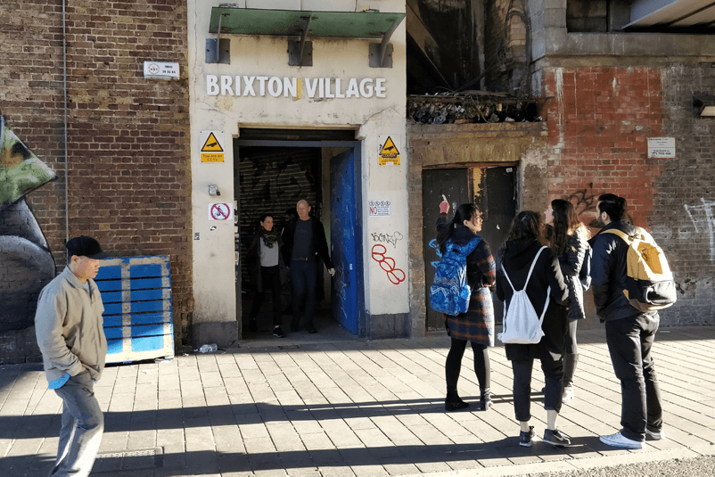 team waiting outside of brixton village