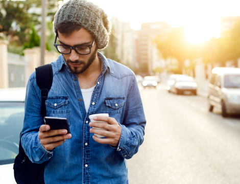Trendy hipster checking phone outdoors