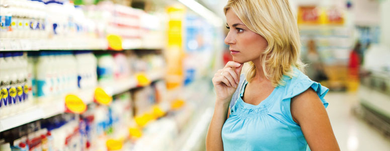Woman deciding what to buy in supermarket
