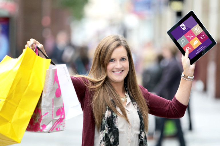 Happy woman with shopping bags and tablet