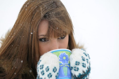 woman drinking hot drink in snow