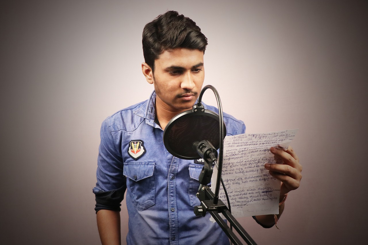 A man stands in front of a microphone reading a script