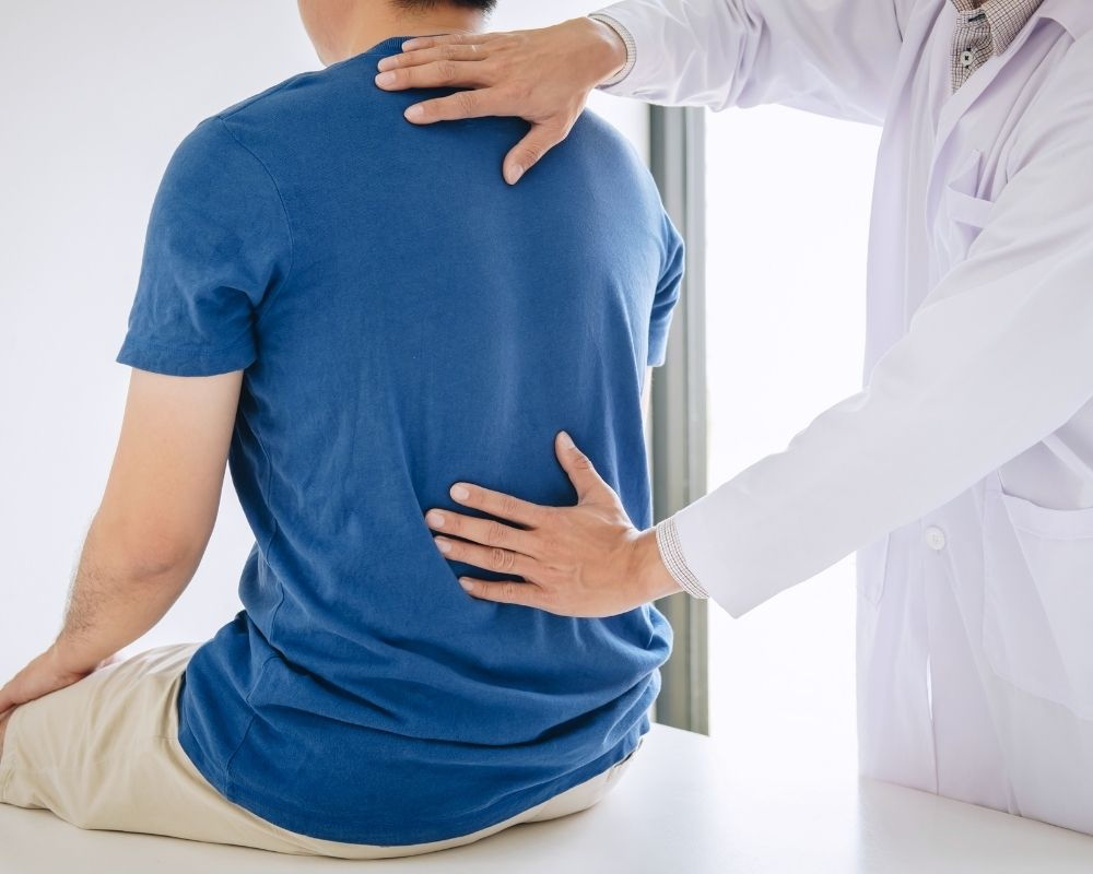 Doctor evaluating spine for herniated disk