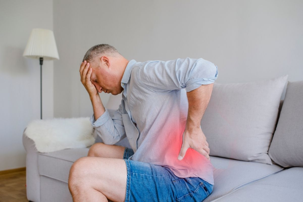 A man grasping his back in pain