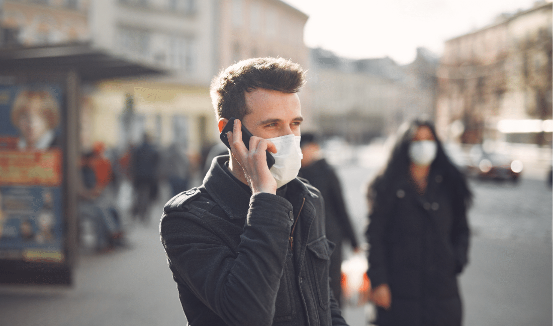 A man with a face mask calling on his cellphone.