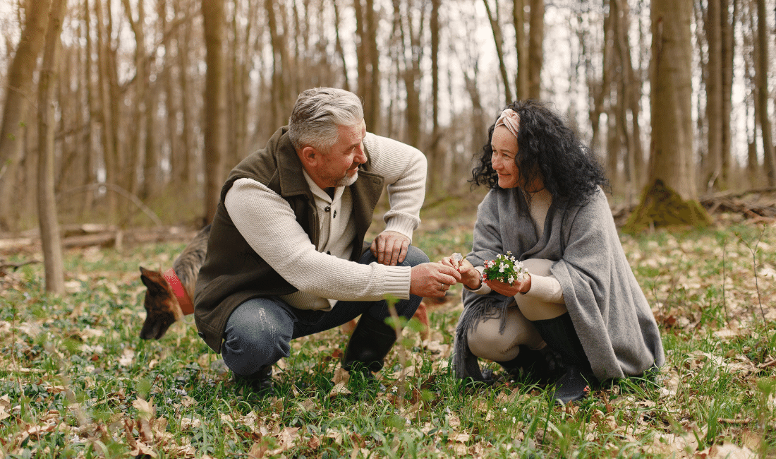 Happy elderly couple in love with fresh flowers and dog in forest