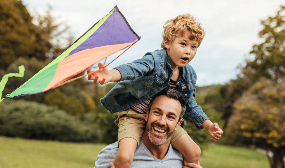 Happy Father and Son Flying Kite Outdoors