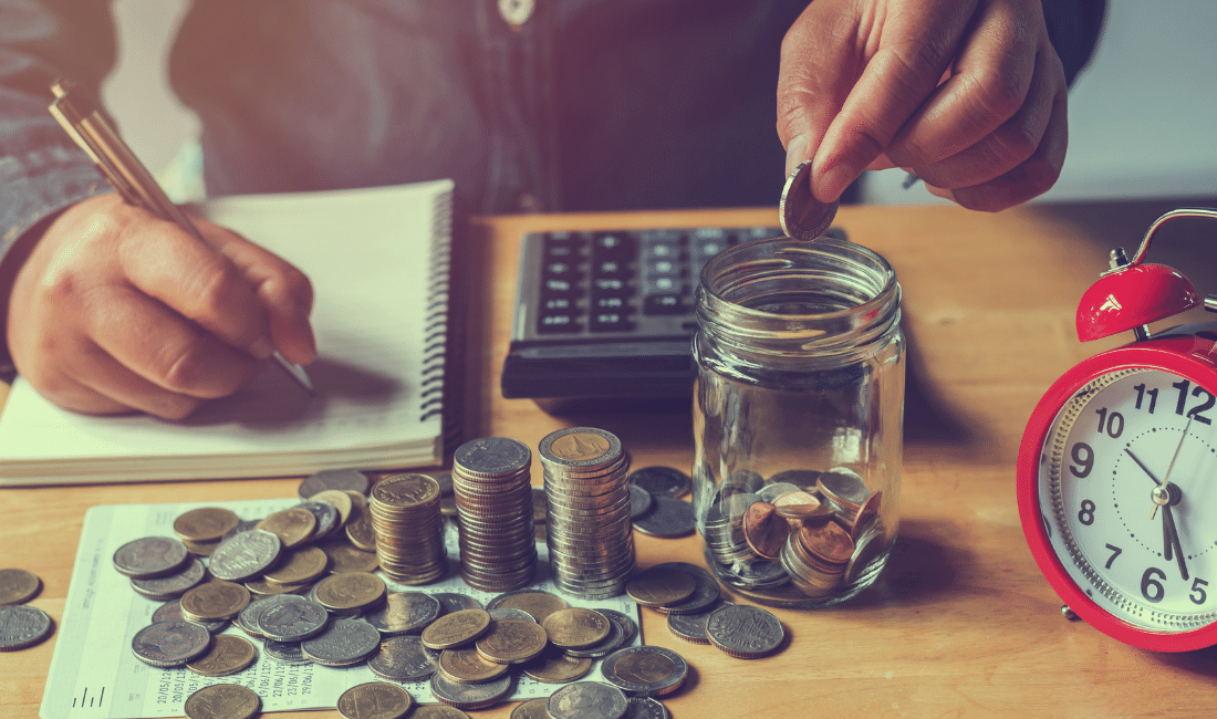 A Person calculating their savings for life insurance with a calculator, as he is dropping coins in a glass jar.