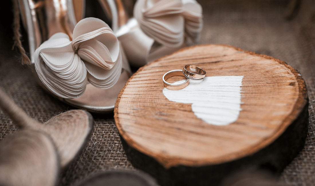 Two wedding bands on wood block.