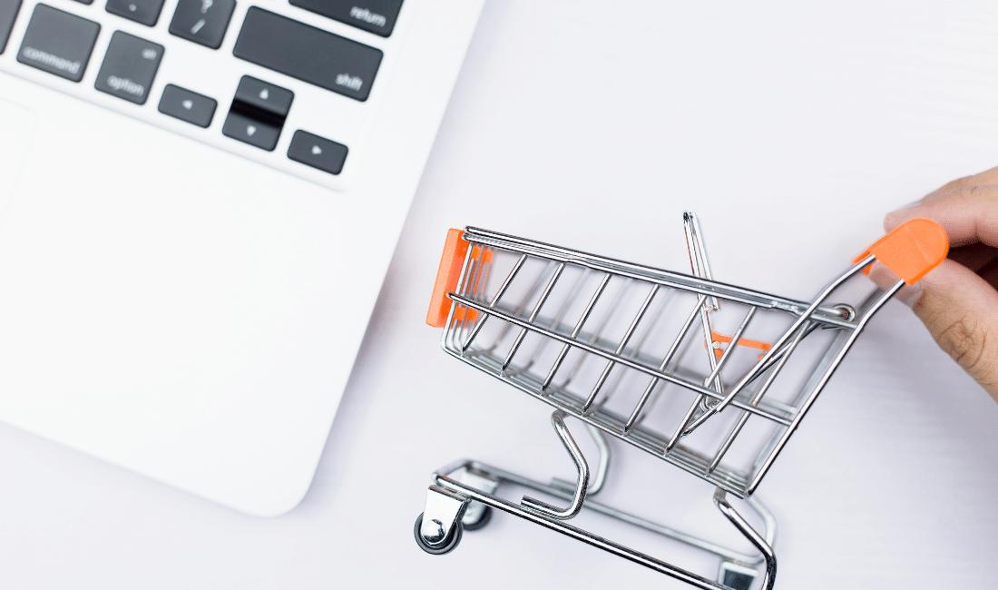 A mini shopping cart beside a laptop computer.