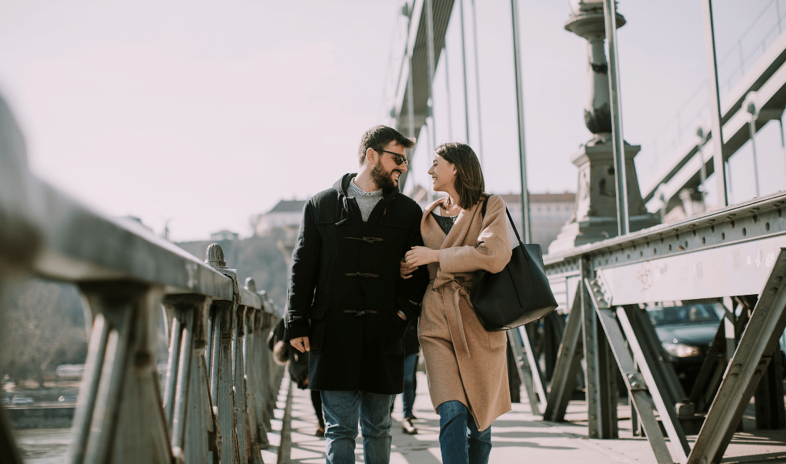 Happy couple walking on a bridge.