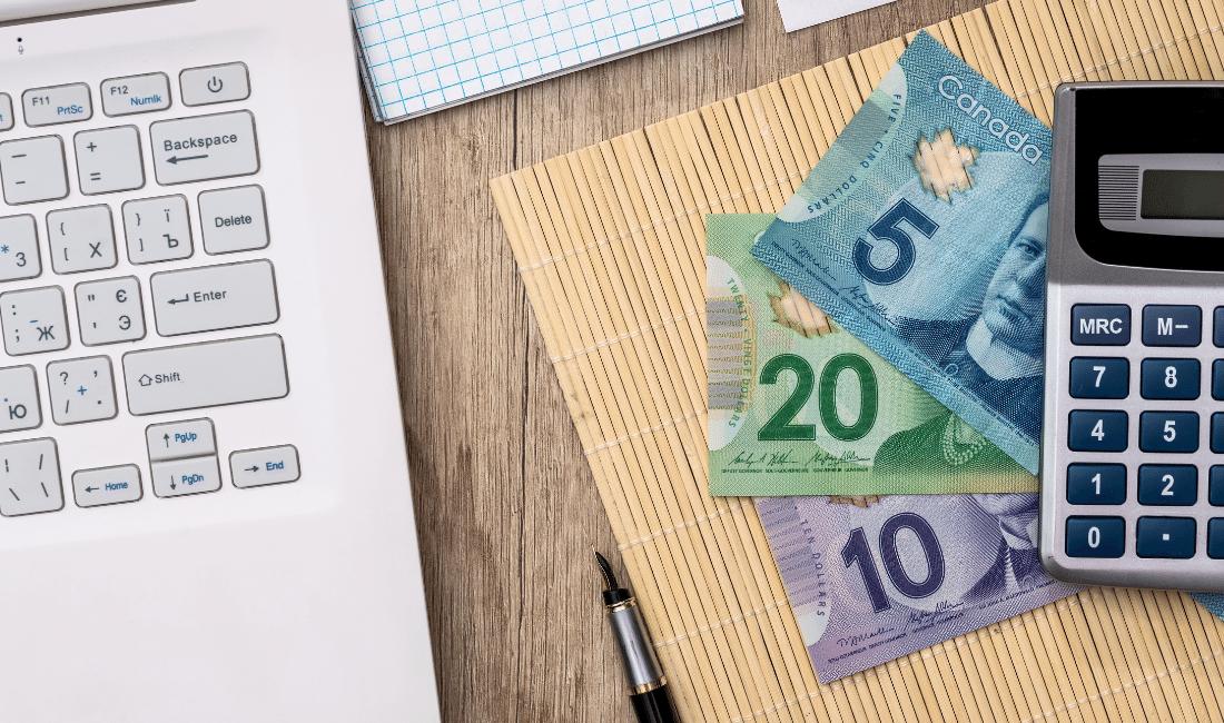 Money and a calculator beside a laptop