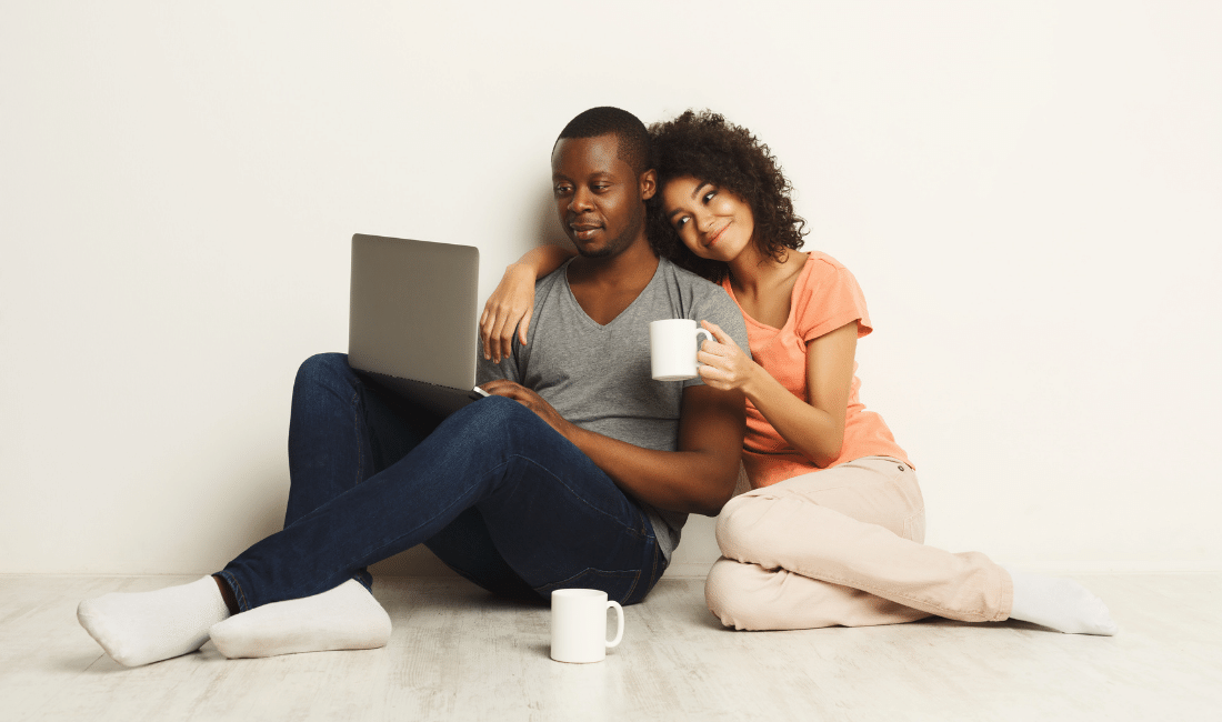 Happy african-american couple shopping for life insurance online on a laptop.