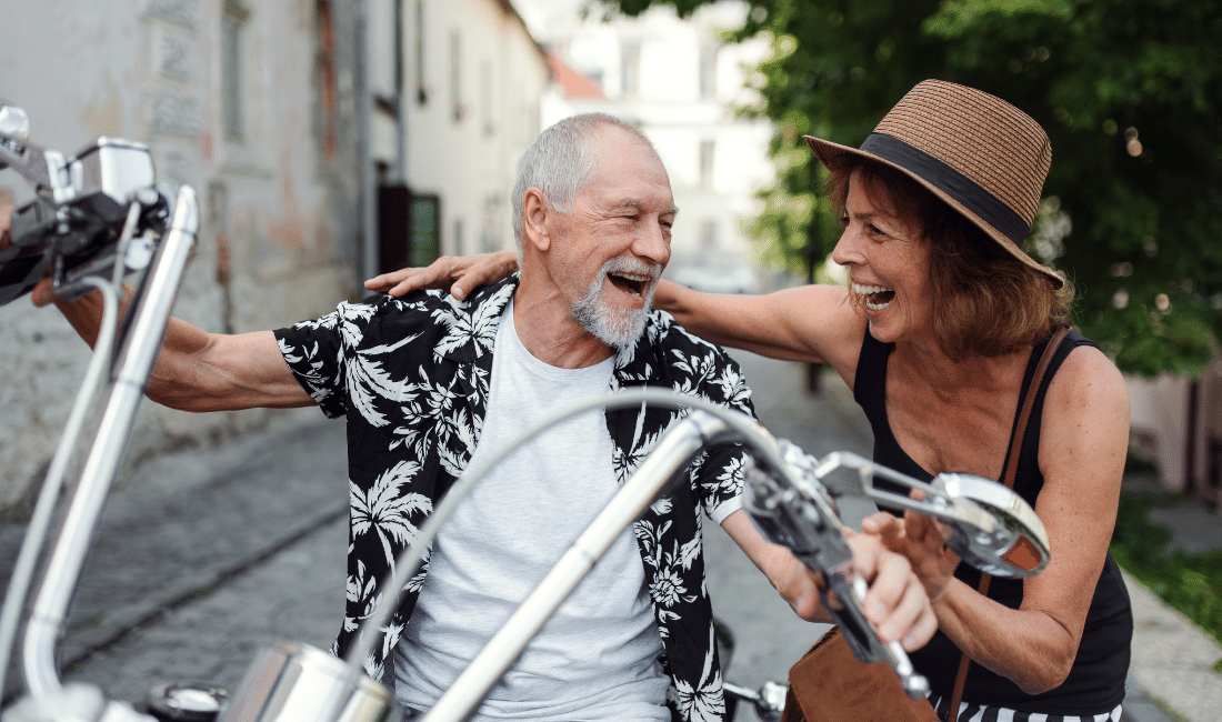 Cheerful Elderly Couple with Motorbike in Town
