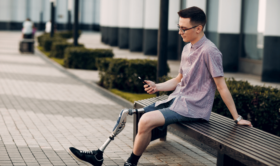Man with Prosthetic Leg sitting in the outdoors.