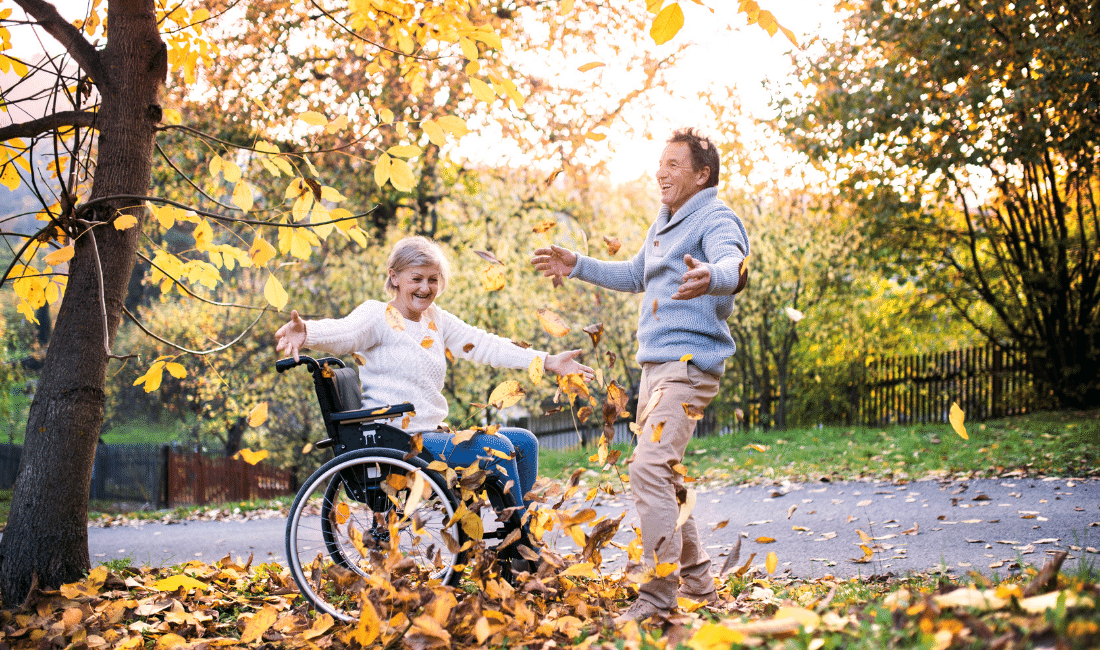 Senior couple in a wheelchair enjoying the outdoors in a park.