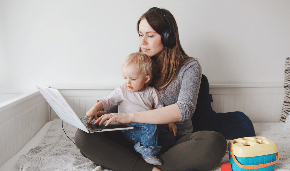Mother with her baby looking at life insurance options on Laptop from home