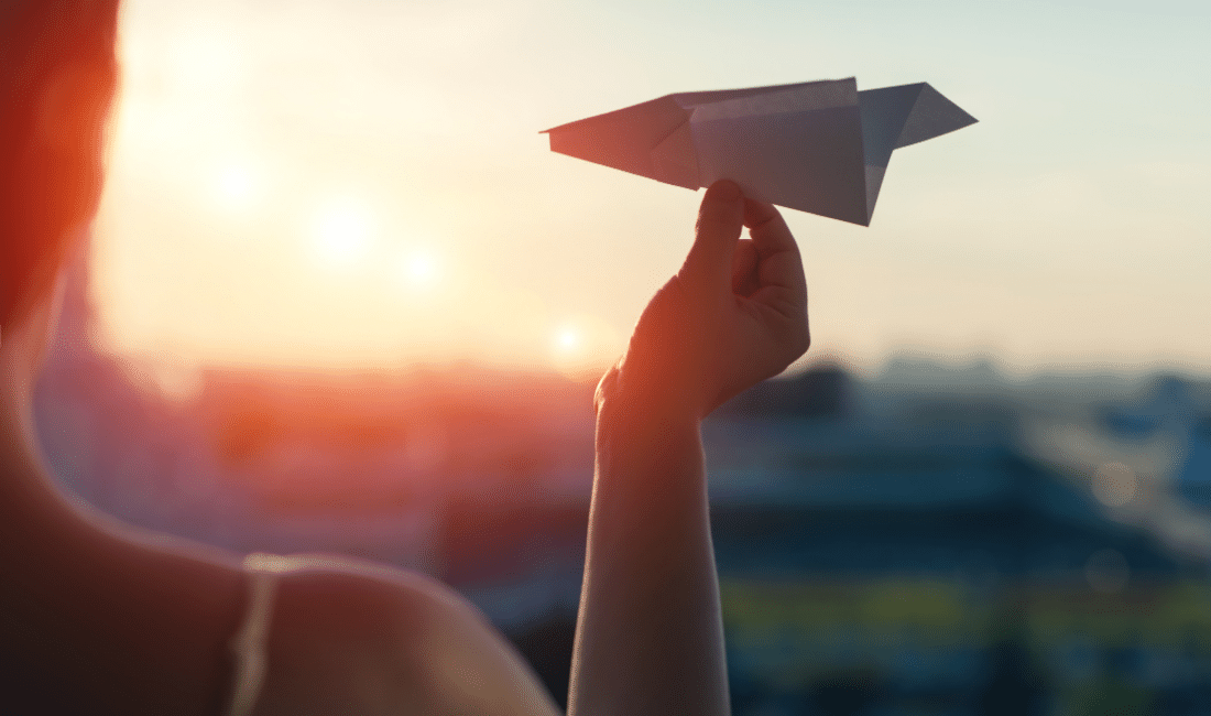 A girl is launching a paper airplane from a window