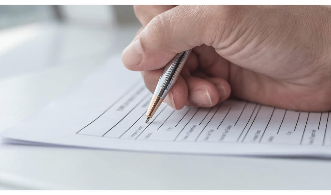 Hand signing a life insurance form