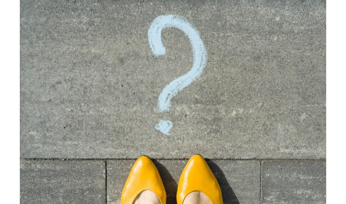 Woman standing behind question mark,