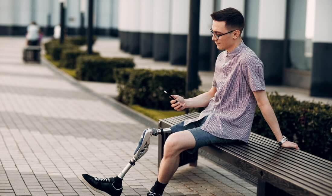 Man with prosthetic leg sitting on a bench