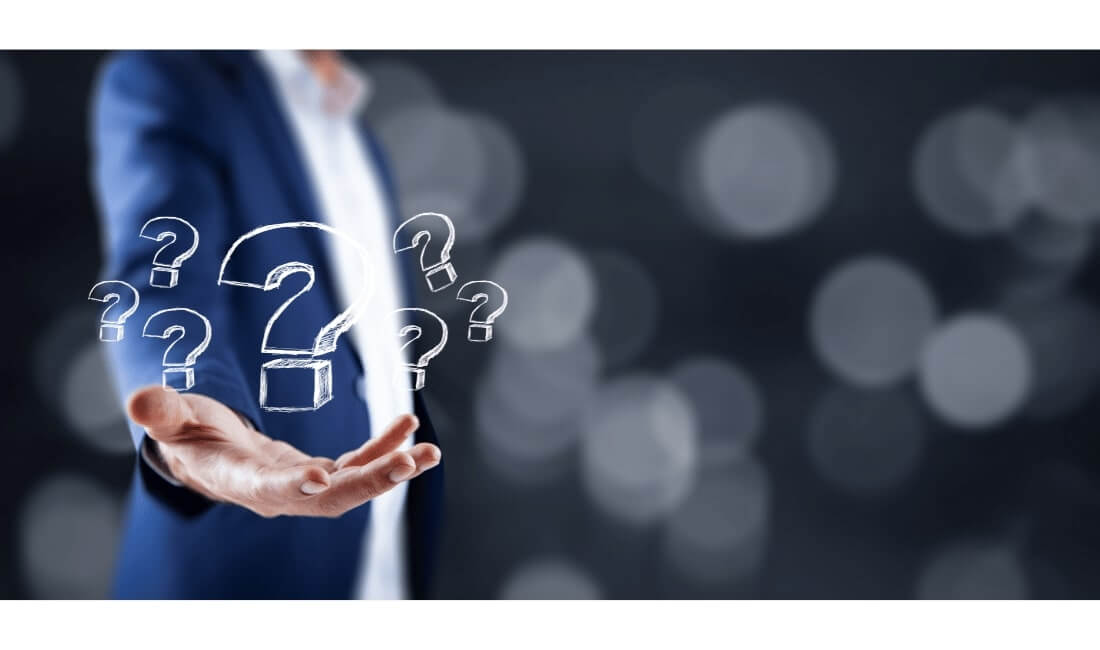 Multiple question marks out of man's hand