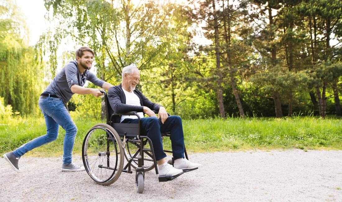Old man on a wheelchair with carer