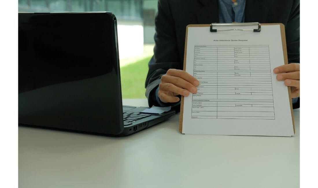 Businessman holding out an auto insurance quote request form