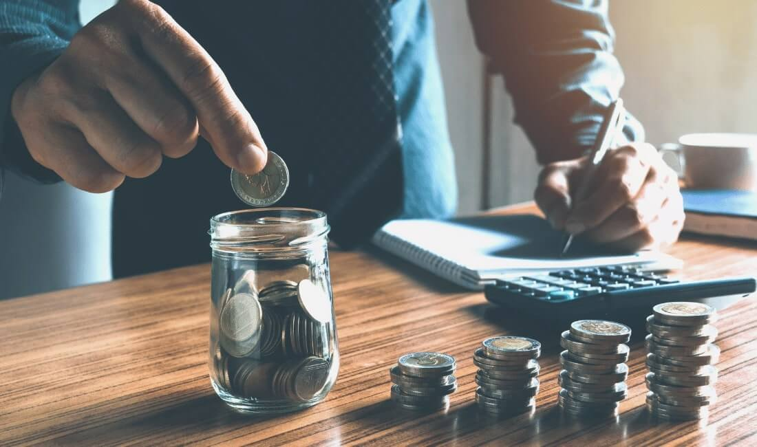 man putting coin in jar while calculating money