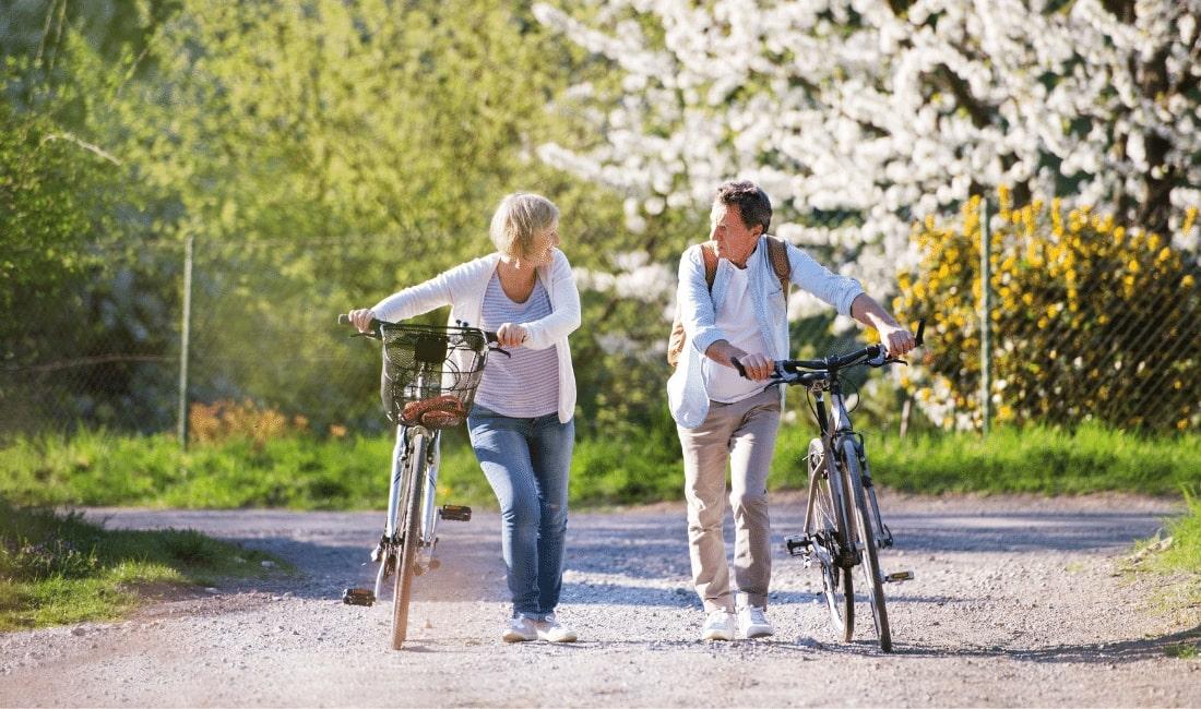 Elderly Couple Pushing Bicycles
