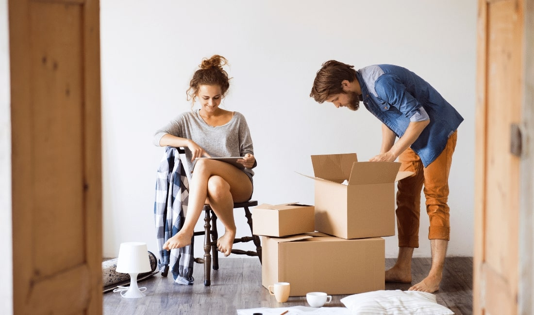 Woman on chair reading notes and man unpacking boxes