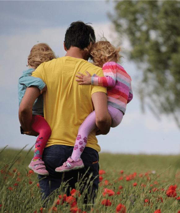 man holding their children in a grass